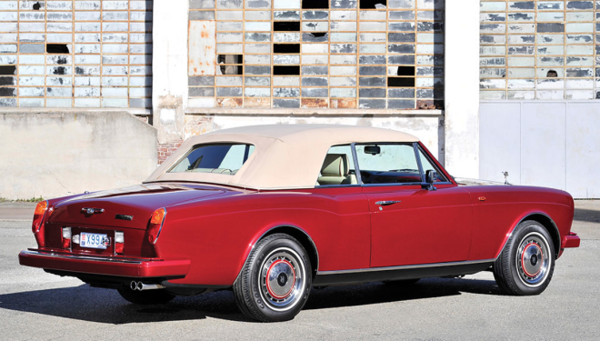 A red Rolls-Royce Corniche with the top up