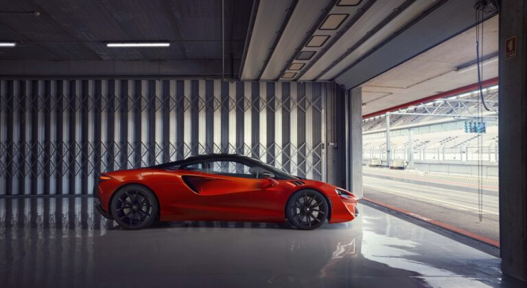 Vermillion red 2022 McLaren Artura in a garage at a racetrack. Buy a McLaren with #pfs_leasing