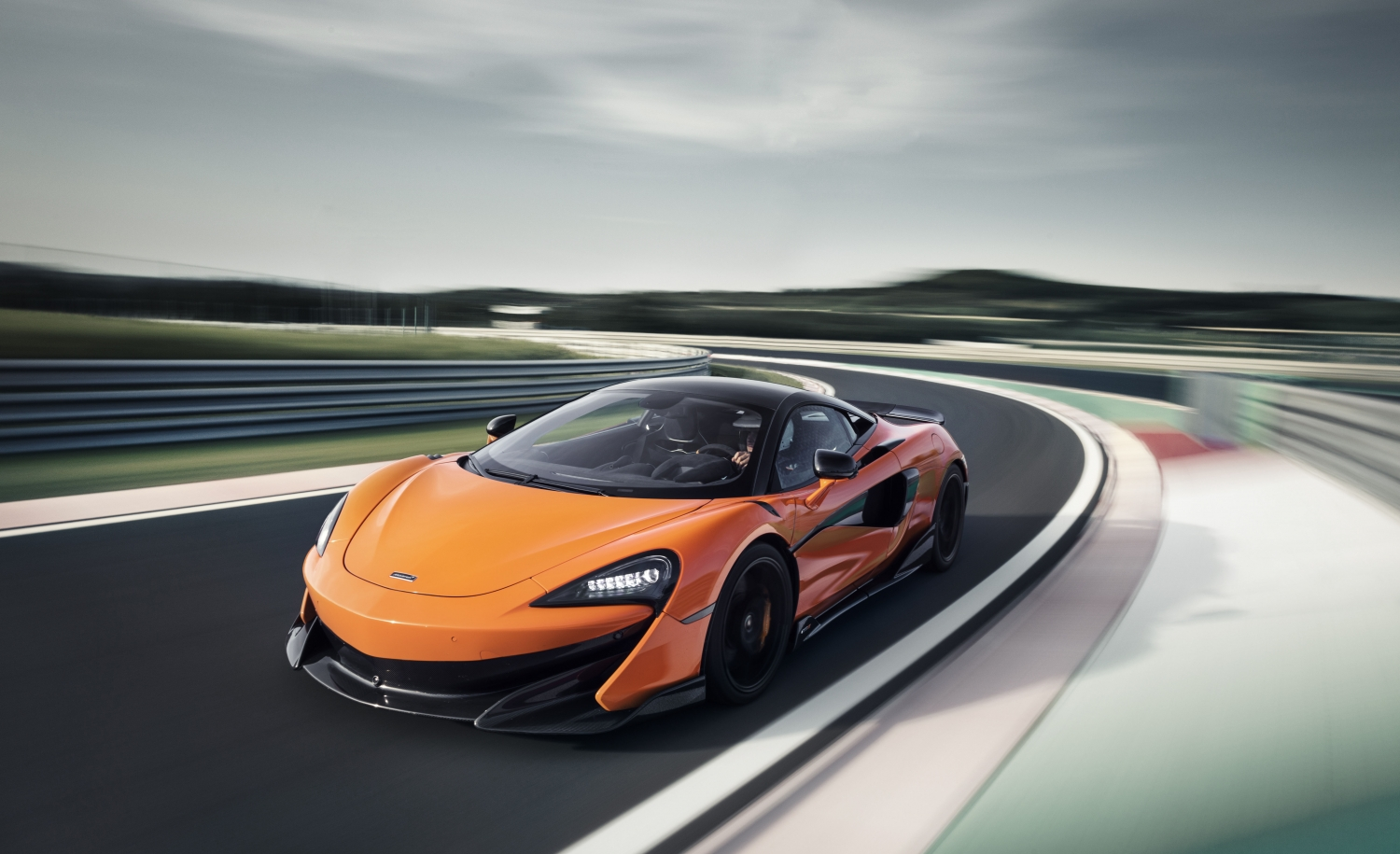 Model Perspective: McLaren 600LT Close Up Action Shot of Orange Longtail Racing On a Track. SportsCar Financing