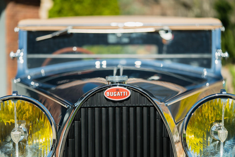 Close up of 1934 Bugatti Type 57, with signature red marque plate and headlamps. Lease a new or vintage Bugatti with Premier's Simple Lease today!