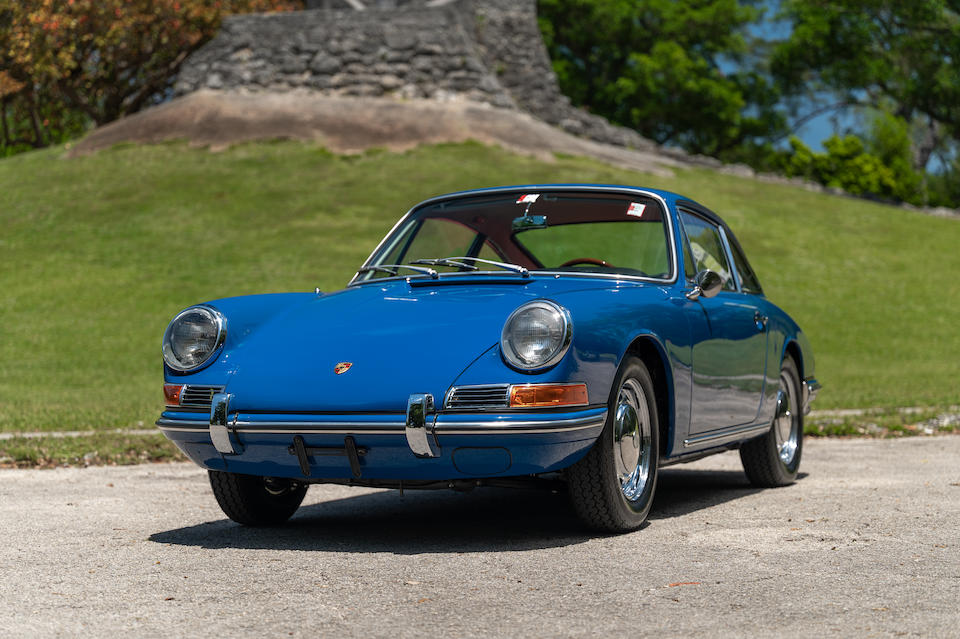 Gulf Blue, glowing blue 1966 Porsche 911 in front of a hill with stone foundation above. Porsche Leasing with Premier. This Porsche alnost looks like it is smiling.