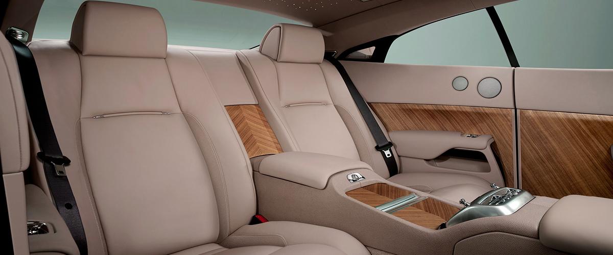 Rear seat of Rolls-Royce Wraith. Ulitmate Leather Luxury, custom wood paneling. Drive a Rolls-Royce