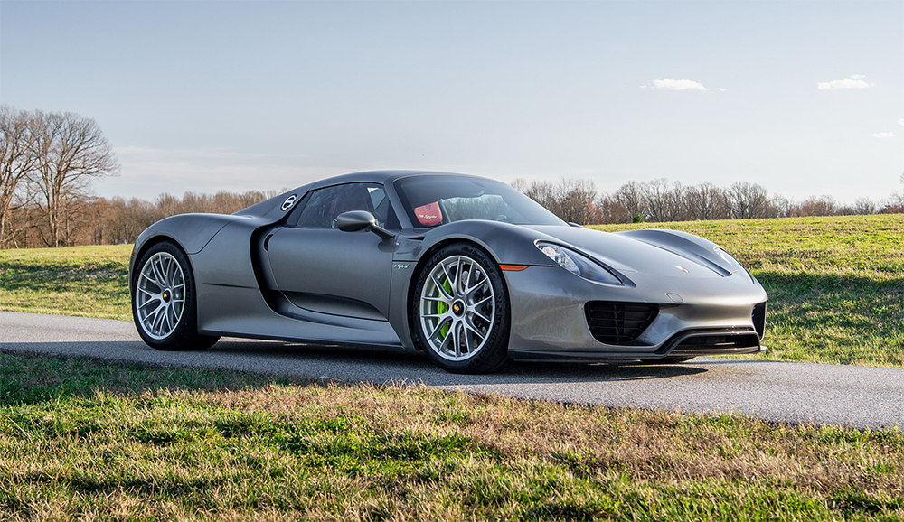 Silver Porsche 918 Spyder front three-quarter view, In grassy field, green calipers; Lease a Porsche with the PFS Simple Lease