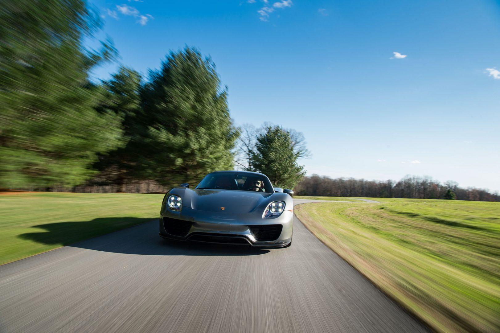 Silver Porsche 918 Spyder in motion front, blurred scenery; Porsche Finance