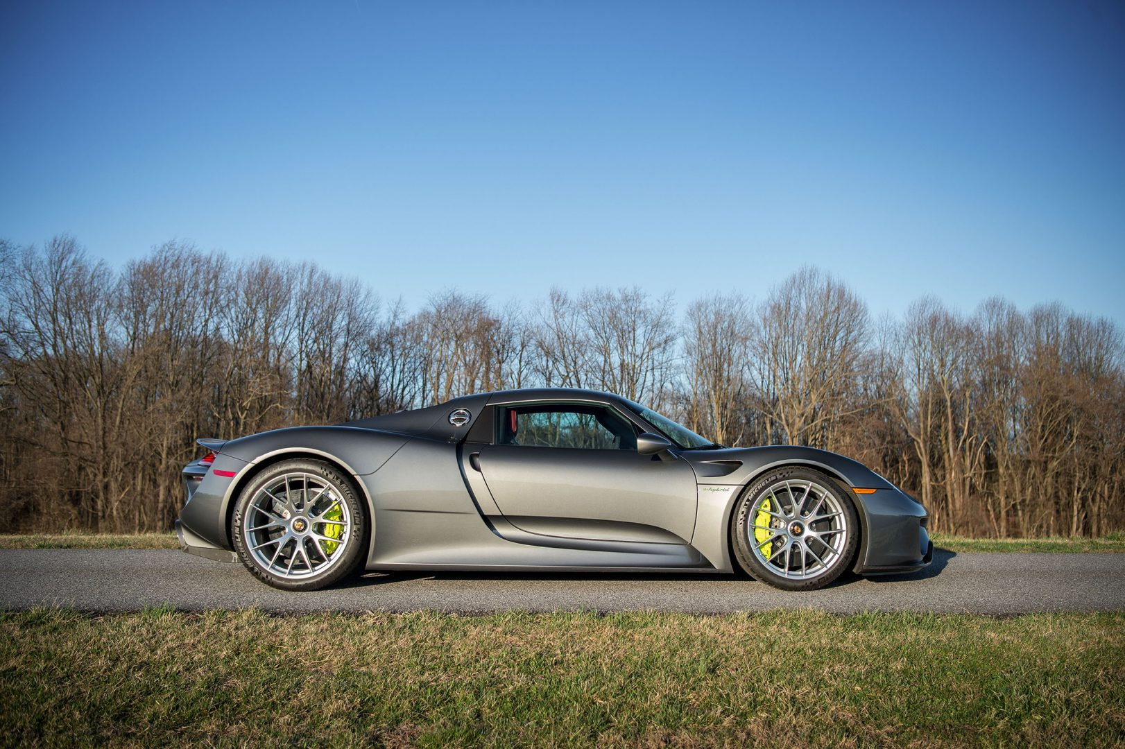 Silver Porsche 918 Spyder profile side view - against early spring trees; #pfs_leasing